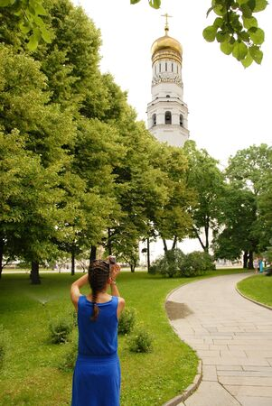 The Ivan the Great Bell Tower in Moscow Kremlin, girl tourist taking photo photo