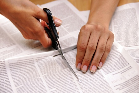 hand with scissors cutting out an article from newspaper