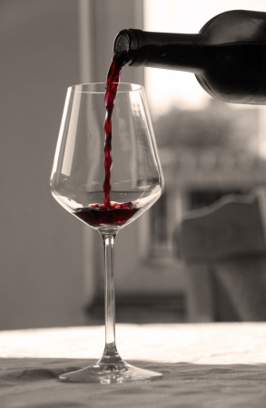 pouring red wine from bottle into wineglass in black and white photo
