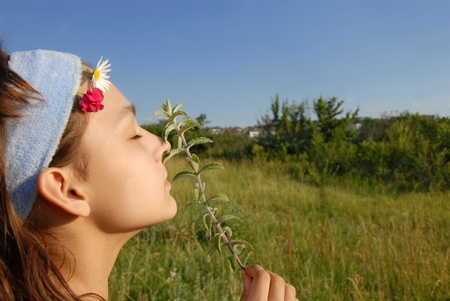 young girl portrait side view smelling a plant on green meadow at summer photo