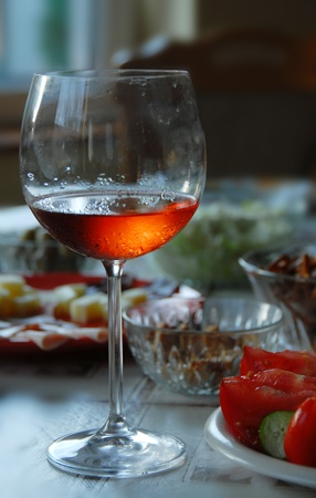 winy: Wineglass with highlighted rose wine on served table