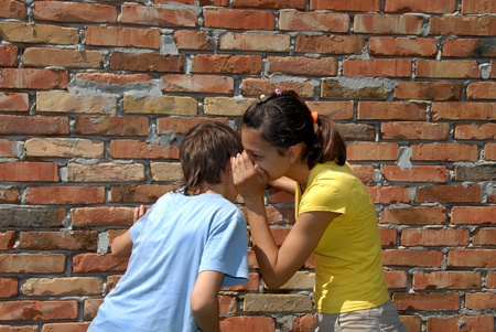 girl telling secret to boy closeup outdoor