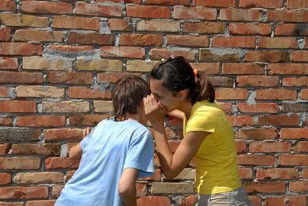girl telling secret to boy closeup outdoor