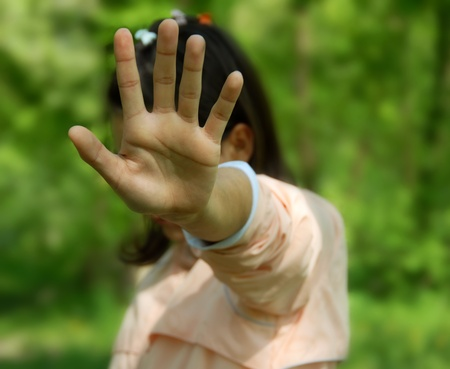 rejection: teen girl covers face by hand as rejection outdoor