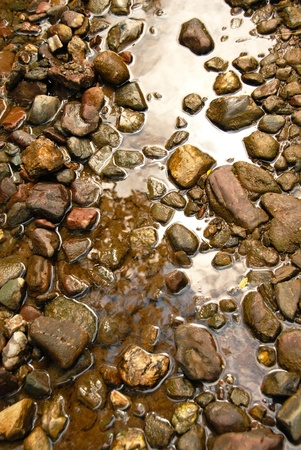 Pebble Beach: brown natural wet rocks in river water background Stock Photo