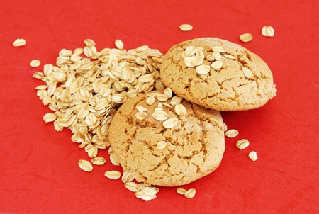 two fresh appetizing oatmeal cookies over red background photo