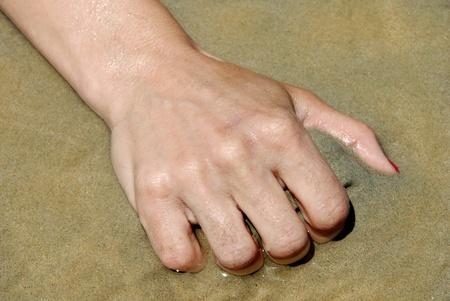 grabbing hand: female hand grabbing sand closeup on seaside outdoors