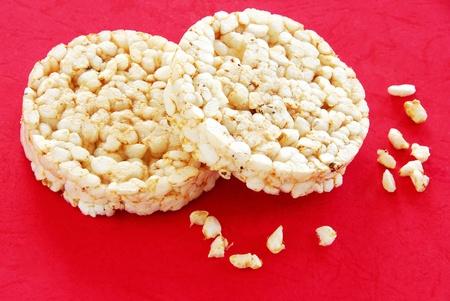 galletas integrales: dos ronda pasteles de arroz sobre fondo rojo