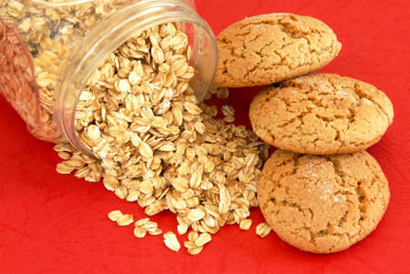 three fresh appetizing oatmeal cookies over red background photo