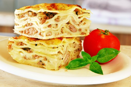 two appetizing lasagna pieces with basil and tomato on white plate photo