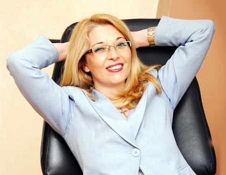 lenguaje corporal: feliz relajada empresaria rubia caucásica en el retrato de gafas en sillón