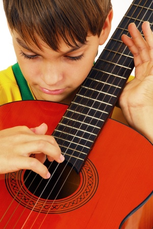 caucasian boy portrait with orange wooden guitar