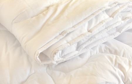 bed spreads: white folded cotton duvet background