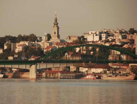 Belgrade cityscape in Serbia, bridge and buildings over water gray toned photo