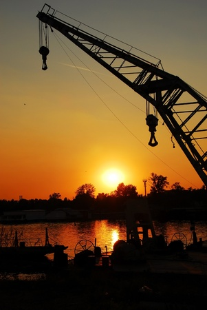 silhouettes on crane in port of Sava river over orange sunset in Belgrade, Serbia photo