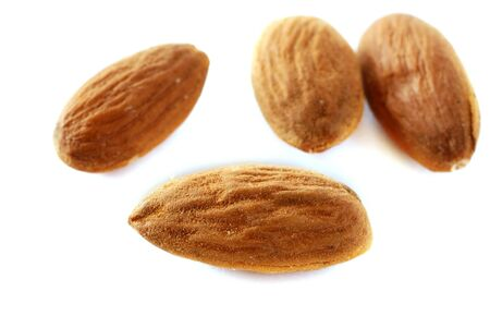 scattered: brown raw almonds over white background macro
