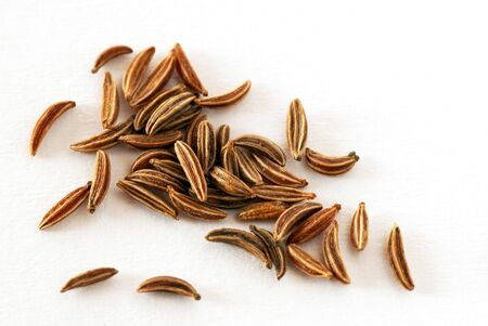 cumin: seeds of dry brown cumin over white background