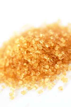 crystallized: heap of yellowish brown sugar over white background
