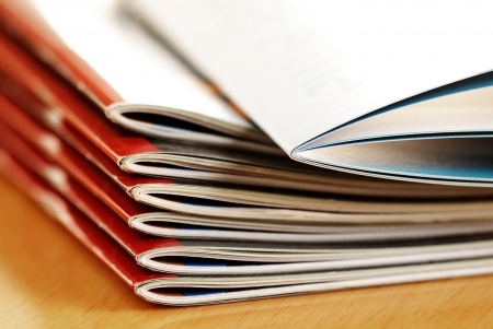 magazine stack: stack of same magazines with red covers closeup Stock Photo