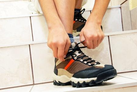 tying: teen boy on stairs tying his shoe closeup Stock Photo
