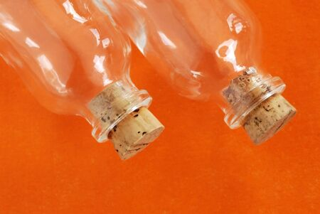 closed corks: two small empty glass bottles closed with corks over orange background