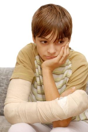 broken wrist: sad teenage caucasian boy with broken arm bone Stock Photo