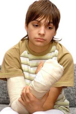 cast: sad teenage caucasian boy with broken arm bone Stock Photo