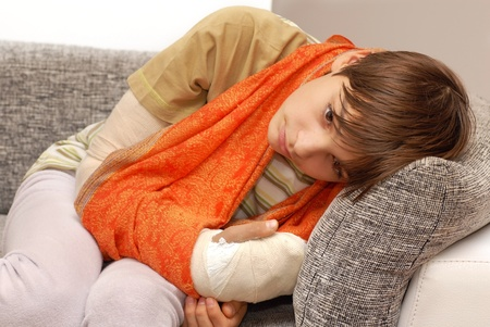 broken wrist: sad teenage caucasian boy with broken arm bone Stock Photo
