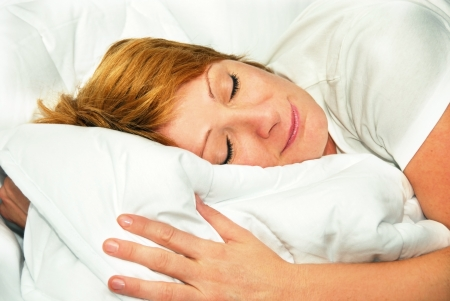 happy smiling caucasian woman portrait lying on duvet indoors photo