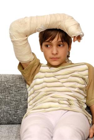 sad teenage caucasian boy with broken arm bone photo