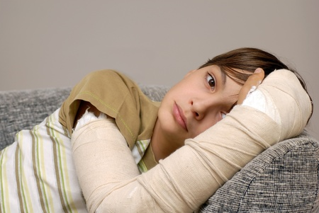 sad teenage caucasian boy with broken arm bone photo