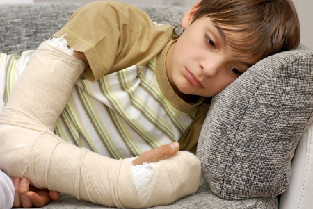 teenage boy: sad teenage caucasian boy with broken arm bone Stock Photo