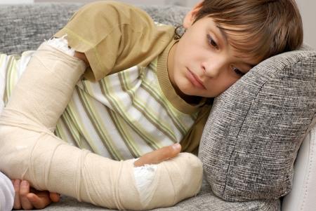 lesionado: triste adolescente caucásico con el hueso del brazo roto