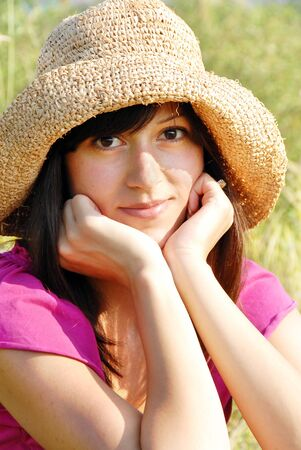 female elbow: young brunette woman portrait outdoor in straw hat