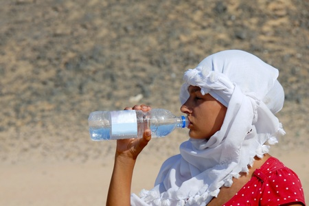 teen girl tourist drinking water in egyptian kerchief in desert