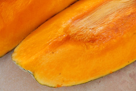 two yellow raw ripe pumpkin pieces closeup photo