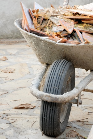 refurbishment: old used wheelbarrow details with construction waste, broken tiles pieces Stock Photo