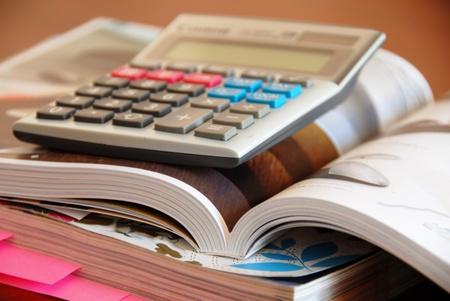 catalogs: two opened dense catalogs and calculator closeup