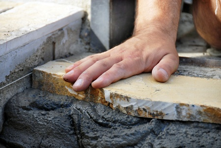 worker hand closeup lying flagstone on concrete Stock Photo