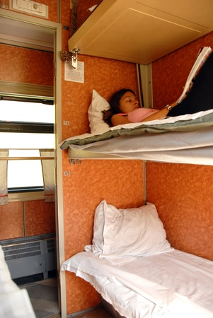 girl lying and reading a book in sleeping wagon in train photo