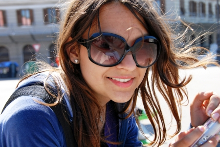 serbian: teenage girl in sunglasses with camera smiling outdoor Stock Photo