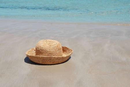 vrouwelijke gele hoed op het strand met blauwe zee Stockfoto