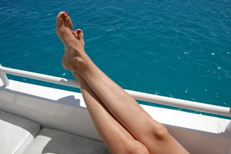 cross leg: mujer cruz� las piernas en el yate de m�s de mar azul