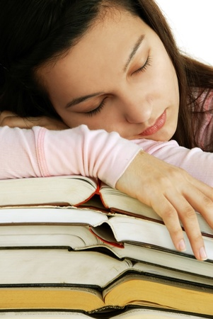 tired caucasian teenage girl portrait sleeping on books stack photo