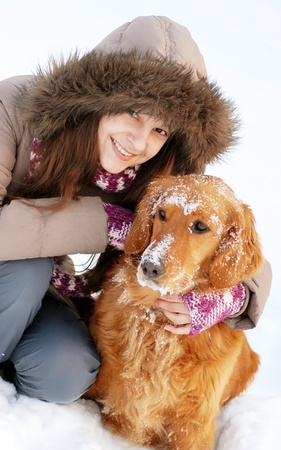 smiling teenager caucasian girl in hood hugging her dog outdoors at snow