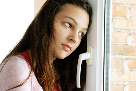 look through window: caucasian teenage girl portrait looking out  window