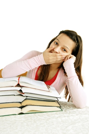 tired caucasian teenage girl sitting at the desk with arm on her mouth, yawning Stock Photo - 13013643