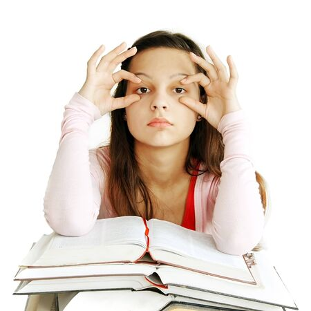eyes opened: tired caucasian teenage girl sitting at the desk with arms holding eyes opened Stock Photo
