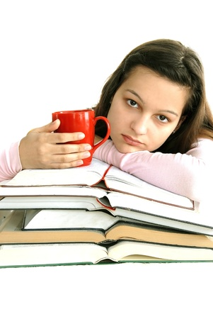 caucasian teenage girl sitting at the desk with stack of opened books and tea cup photo