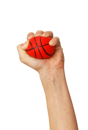 one isolated hand squeezes small sponge basketball toy ball over white background Standard-Bild
